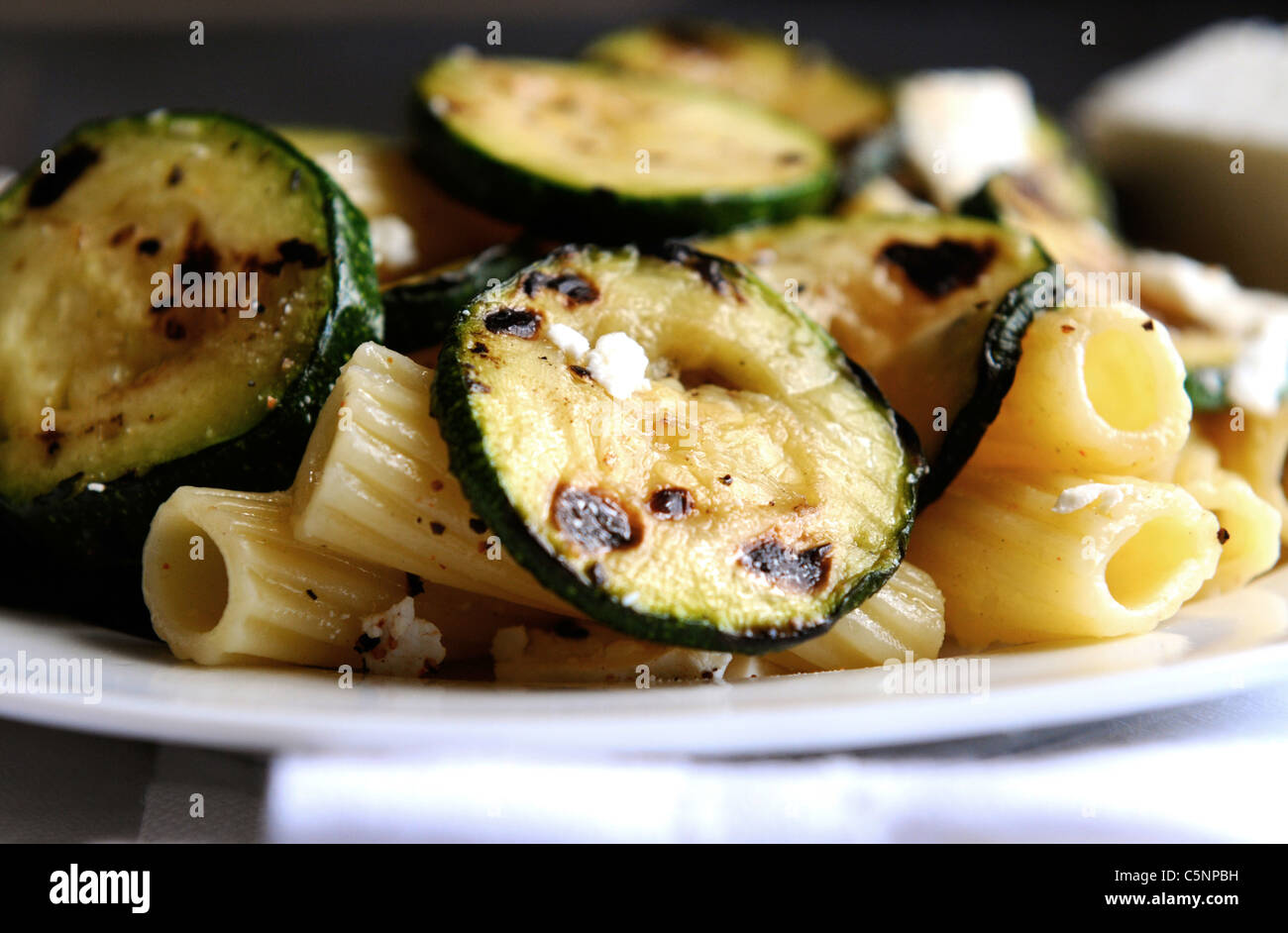 Pasta with fried courgette slices - Stock Image