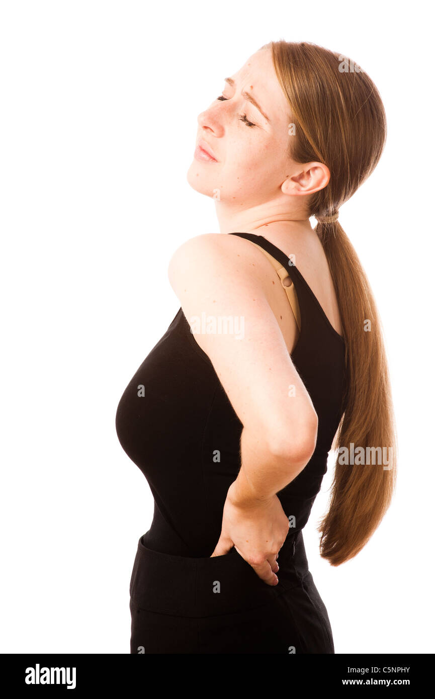a young caucasian woman girl with a pain in her lower back, rubbing her backache for relief - Stock Image