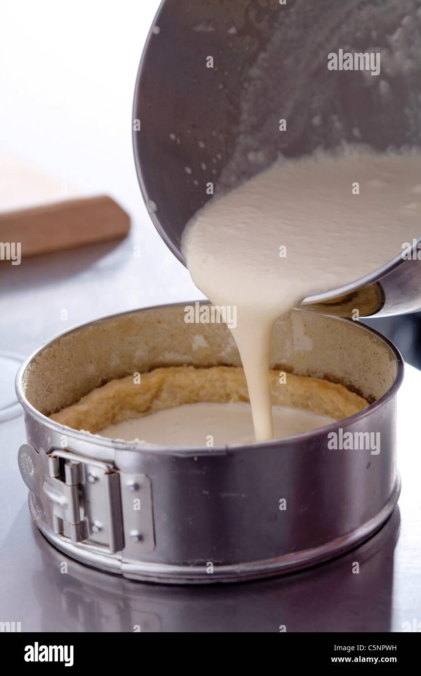 Pouring vanilla cream into shortcrust pastry case - Stock Image