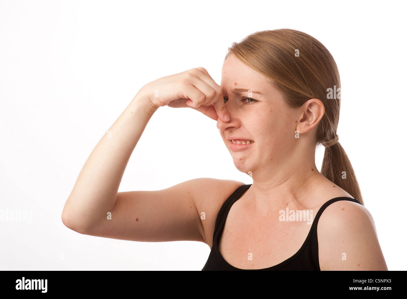 a young caucasian woman holding her nose to alleviate a nasty smelly smell - Stock Image