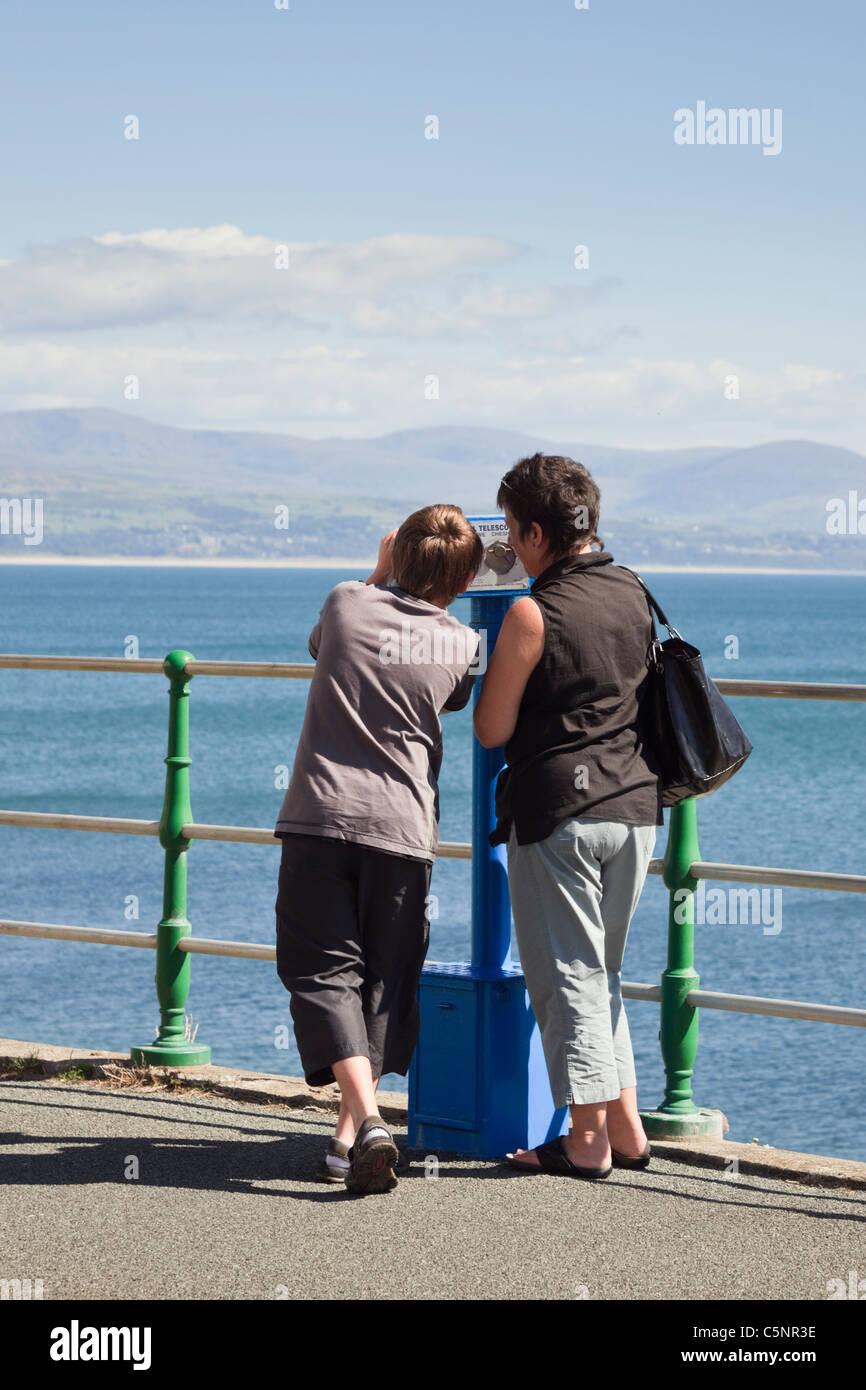 Woman and boy looking for dolphins using an Owl telescope across Cardigan Bay. Criccieth Lleyn Peninsula Gwynedd - Stock Image