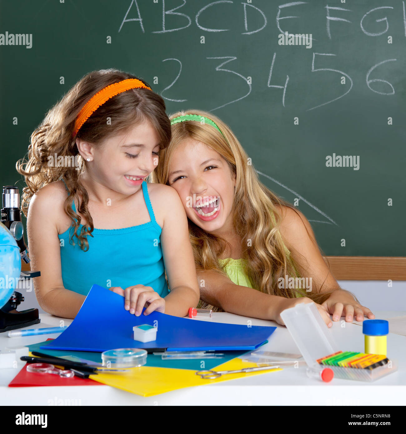 happy laughing kids student girls at school classroom in desk - Stock Image