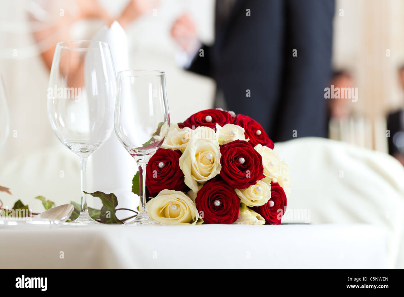 Wedding table at a wedding feast decorated with bridal bouquet - Stock Image