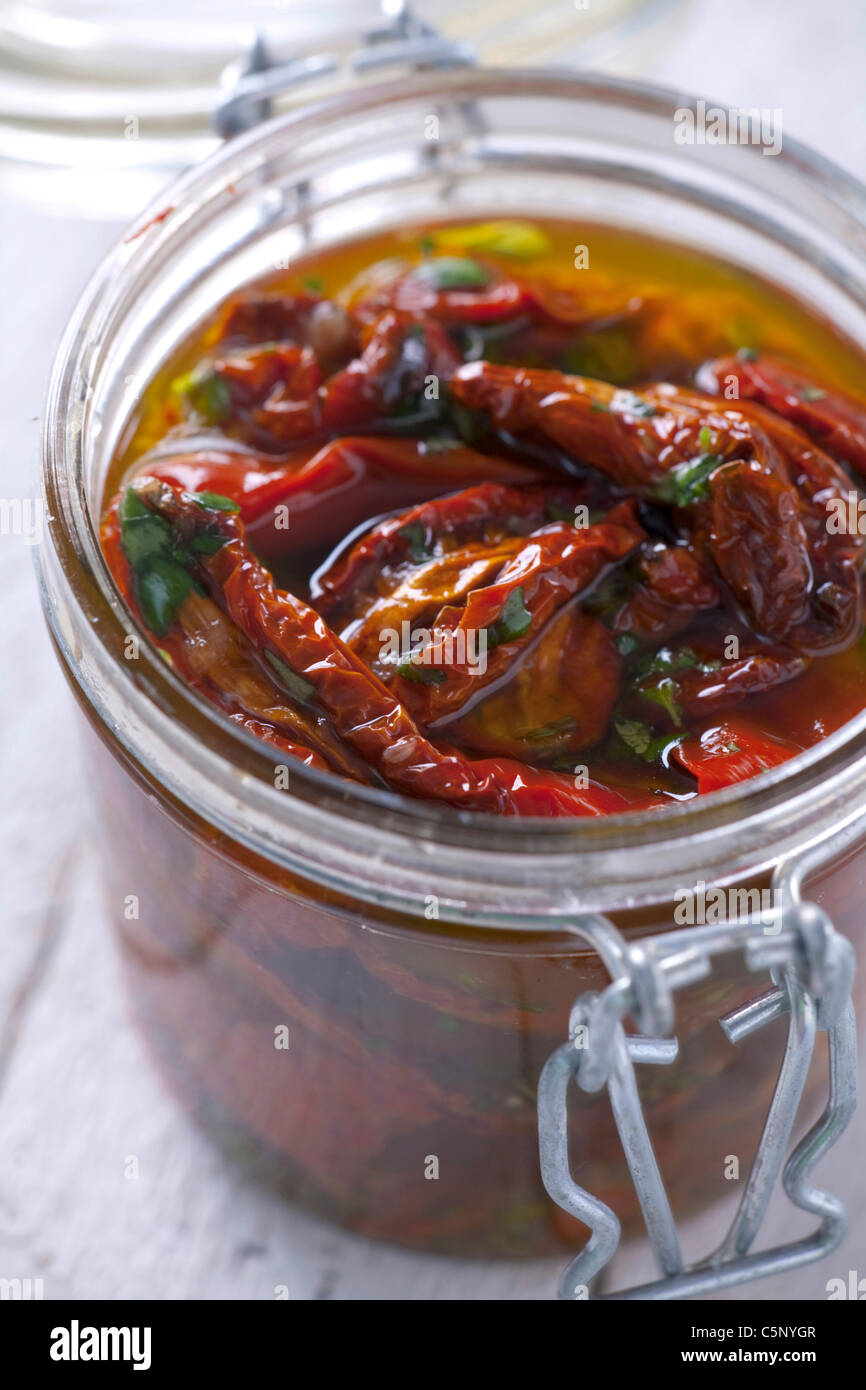 Dried tomatoes in a jar with olive oil - Stock Image