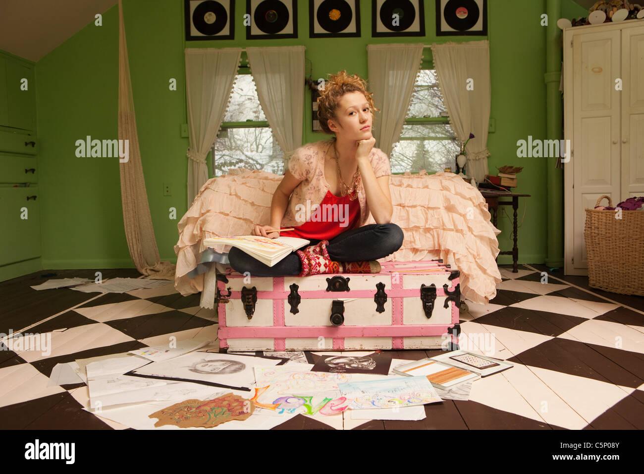 Teenage girl sitting on ottoman with drawings on bedroom floor - Stock Image
