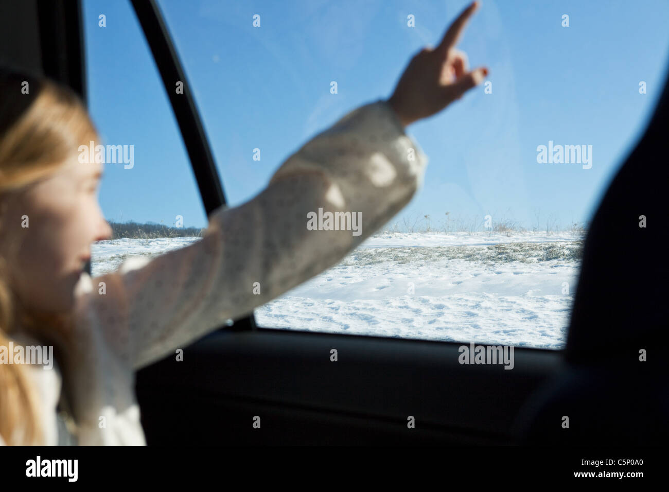 Young girl pointing through car window - Stock Image