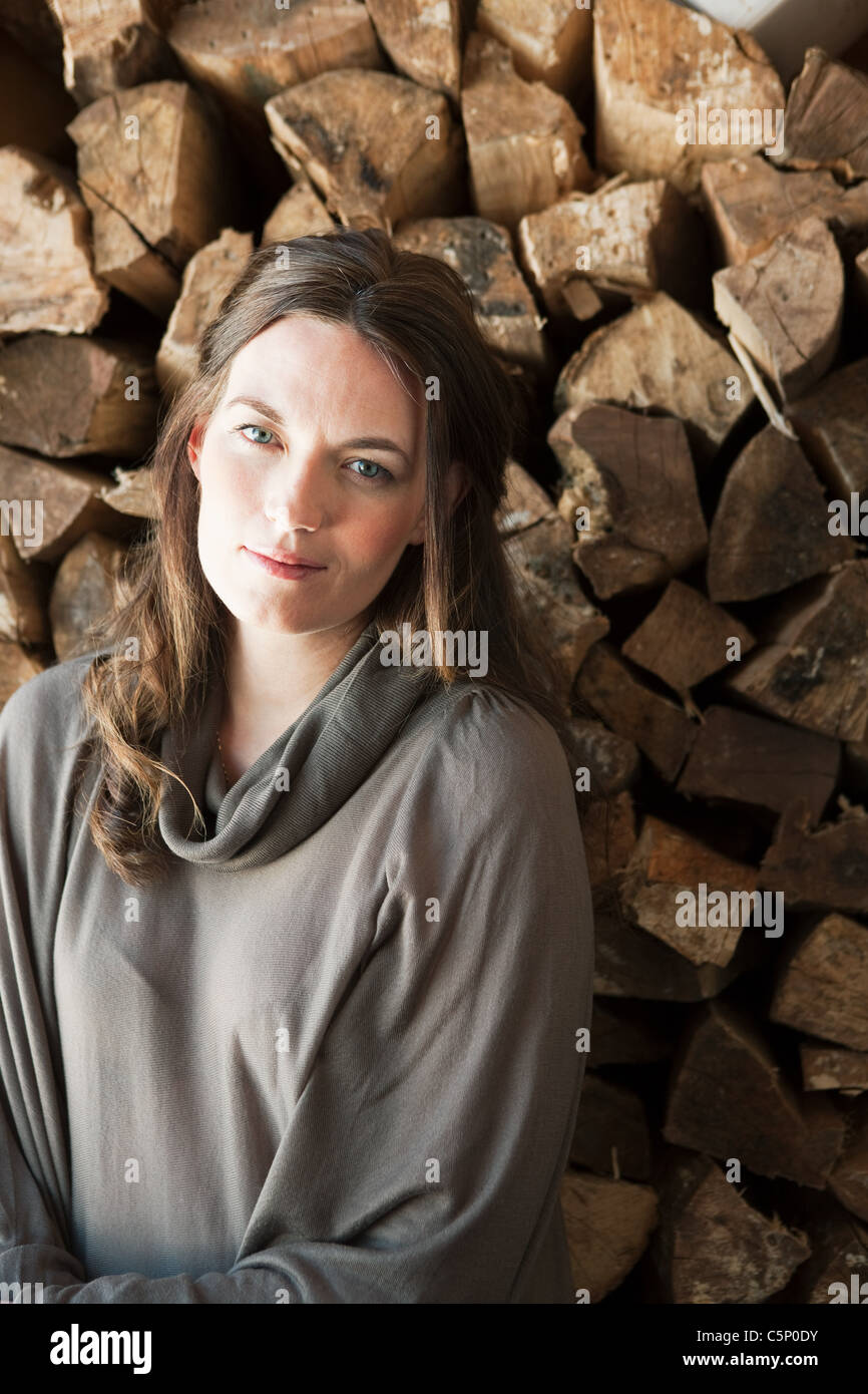 Woman in front of logs, portrait - Stock Image