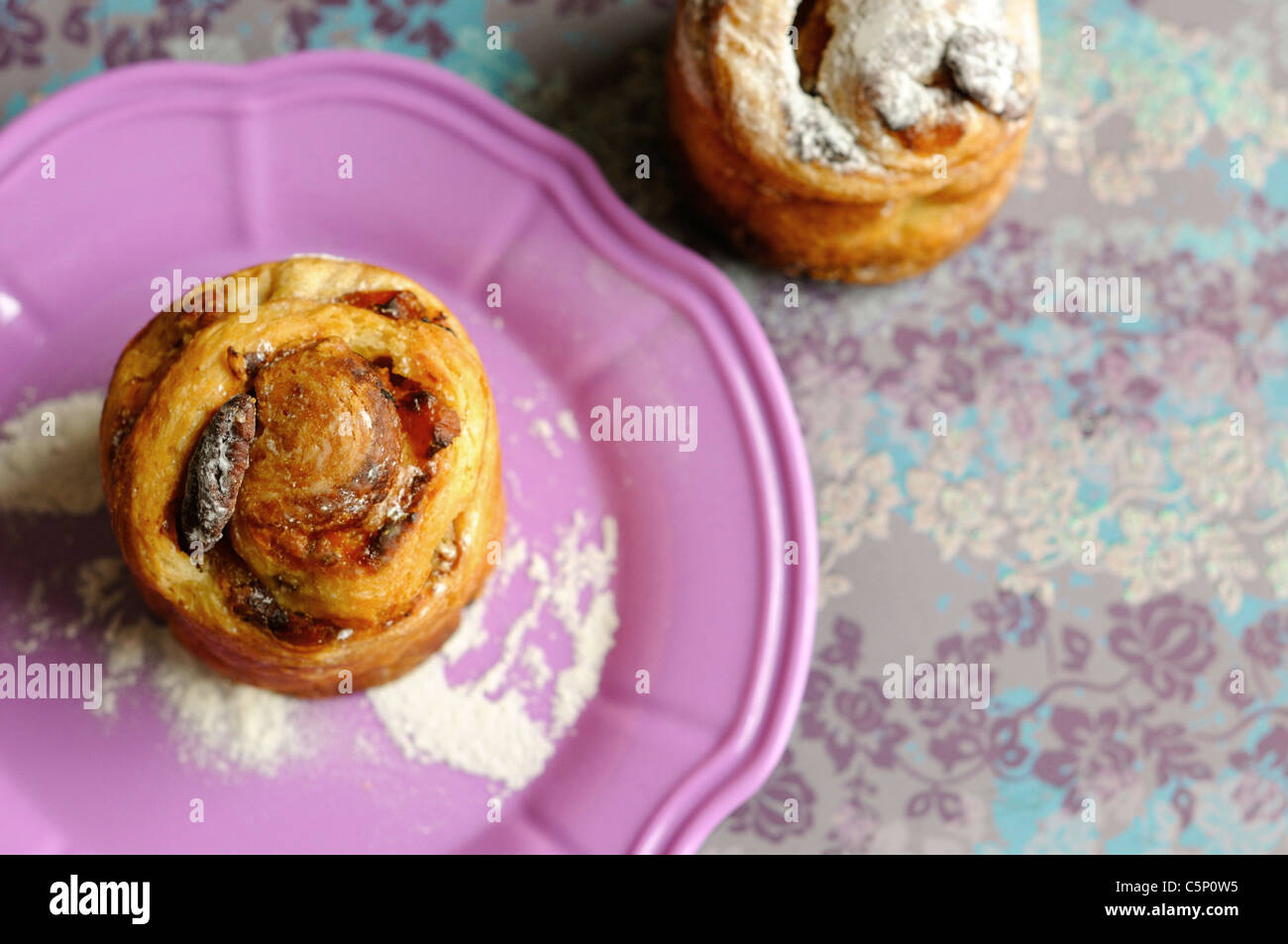 Pecan and  apricots buns on a pinky plate - Stock Image