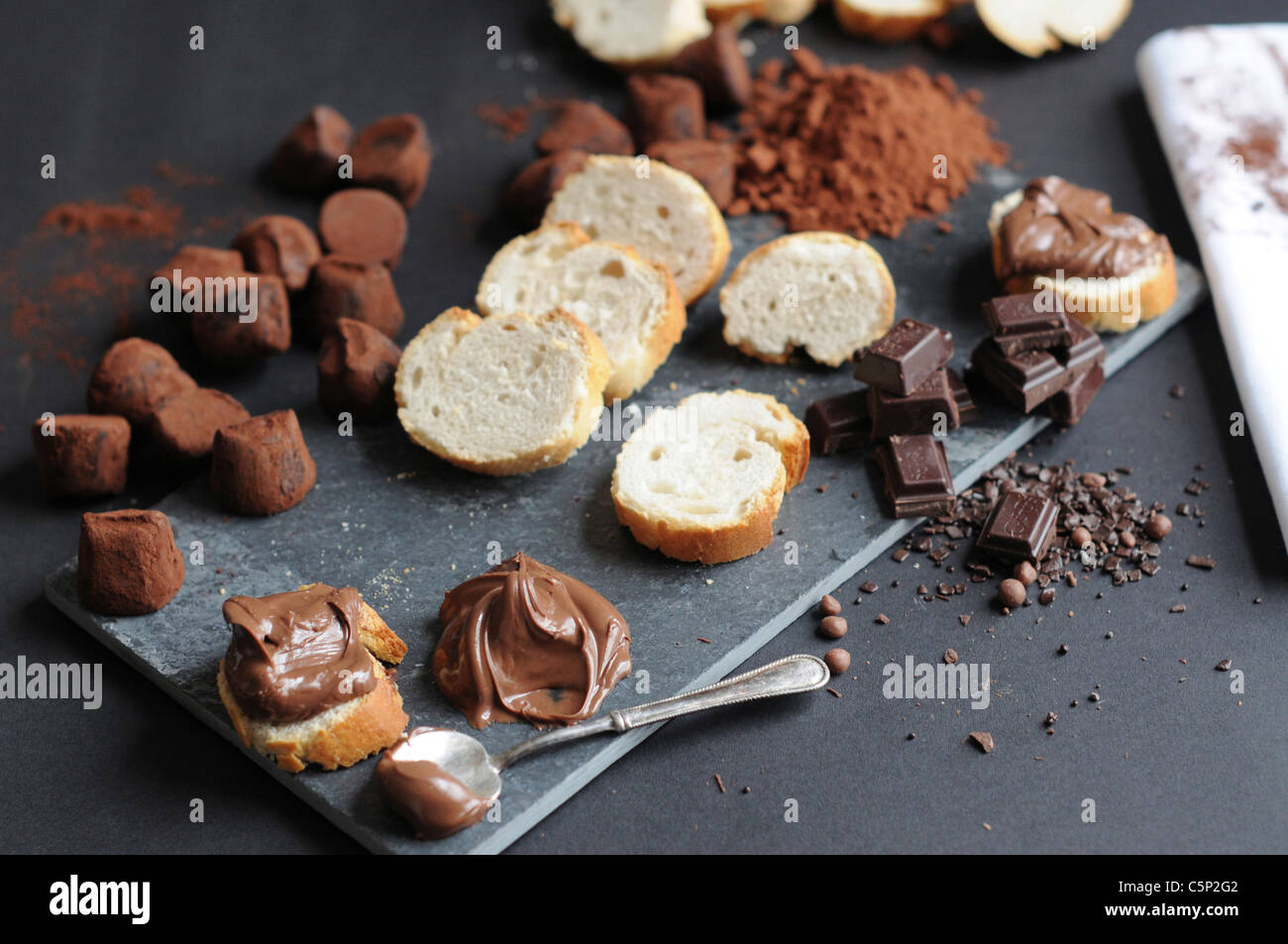 Slices of baguette with chocolate cream, chocolate pieces and truffles, cokoa powder - Stock Image