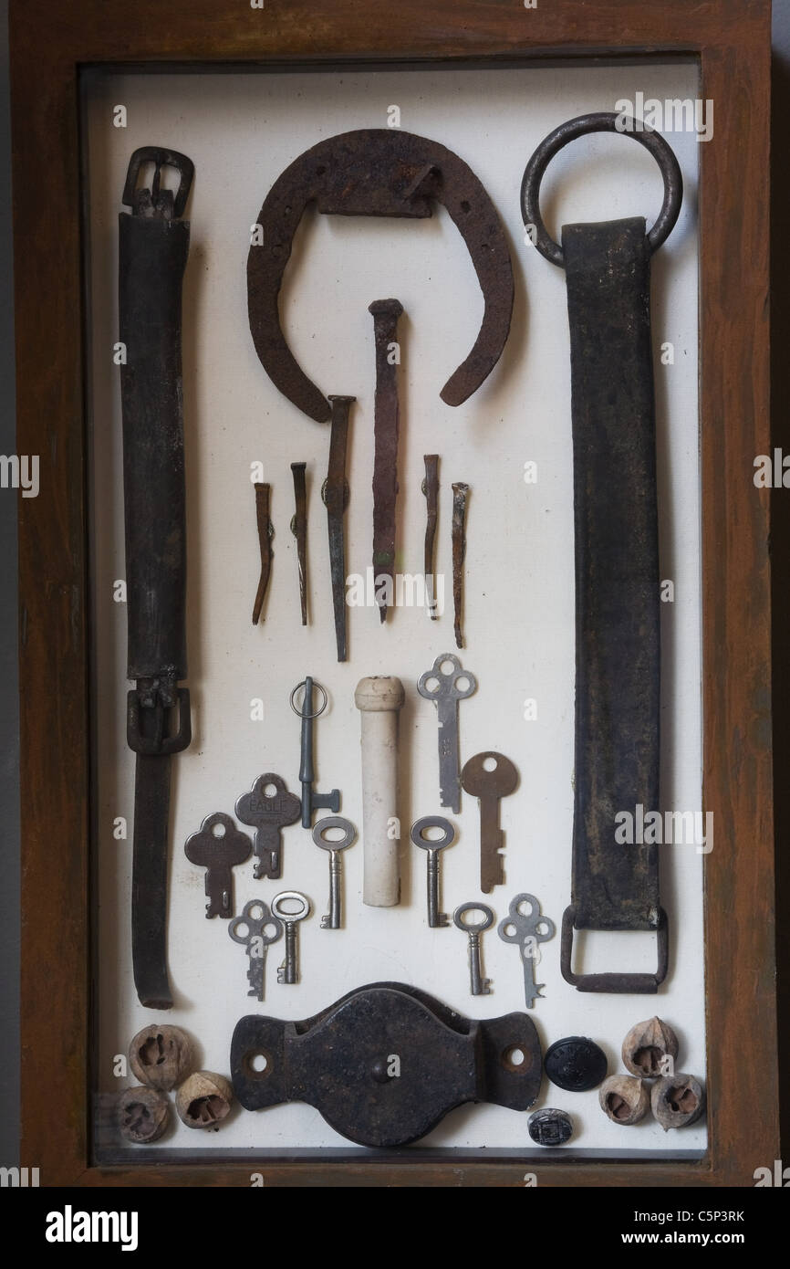 Old iron objects in display cabinet - Stock Image