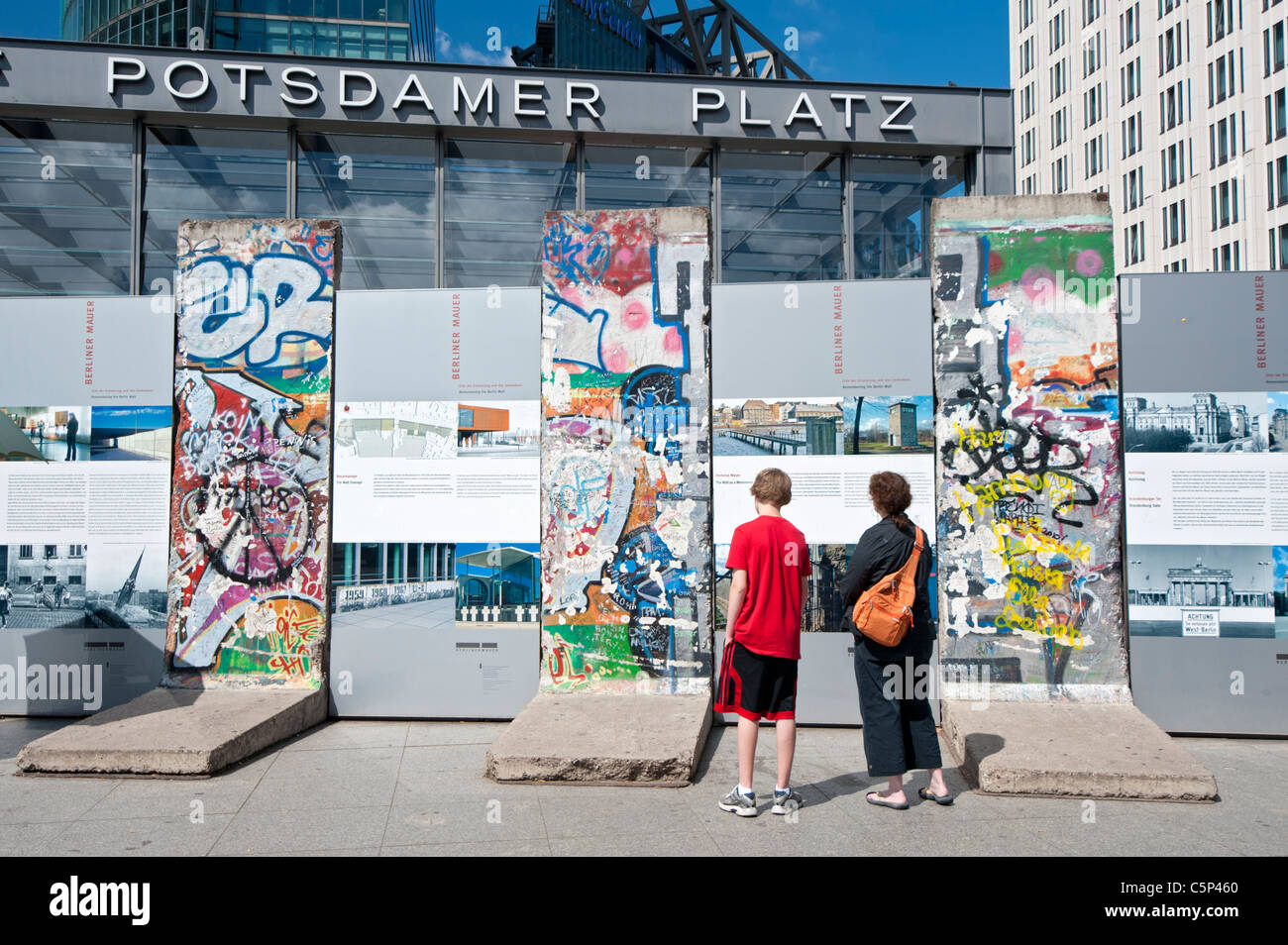 Tourists looking at original sections of Berlin Wall at Potsdamer Platz in Berlin Germany - Stock Image