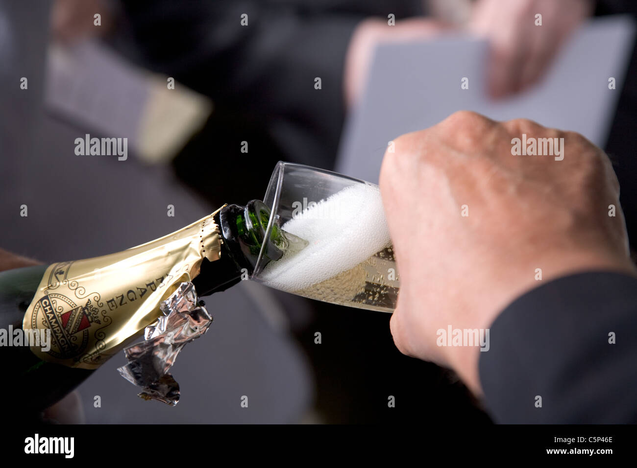 Champagne being poured into a champagne flute at a wedding breakfast - Stock Image