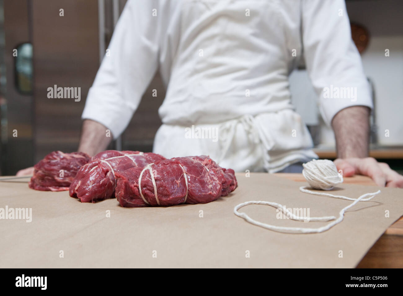 Butcher and beef tenderloin rolled and tied - Stock Image