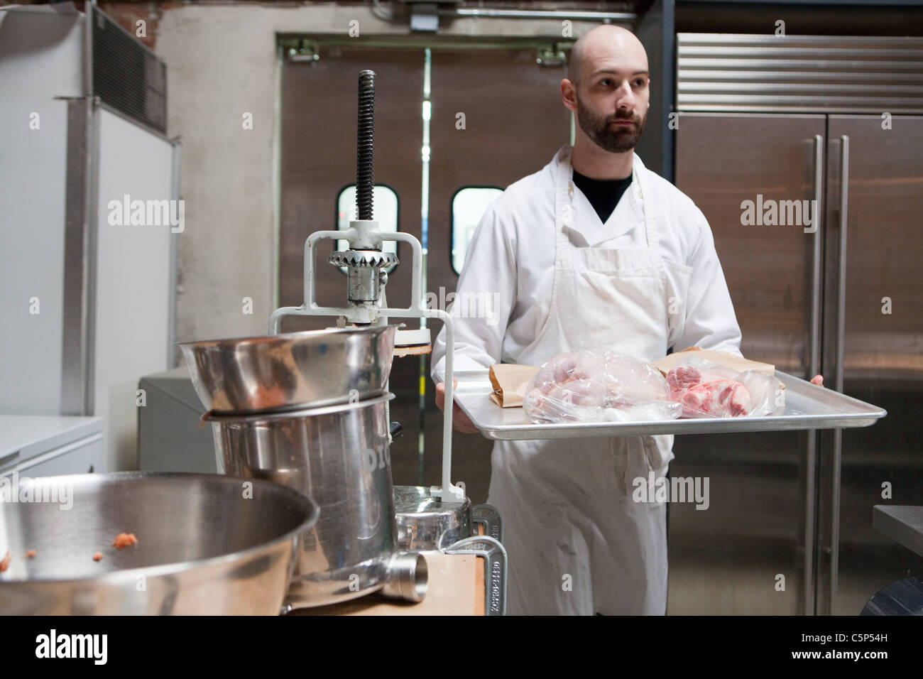 Butcher with tray of meat - Stock Image