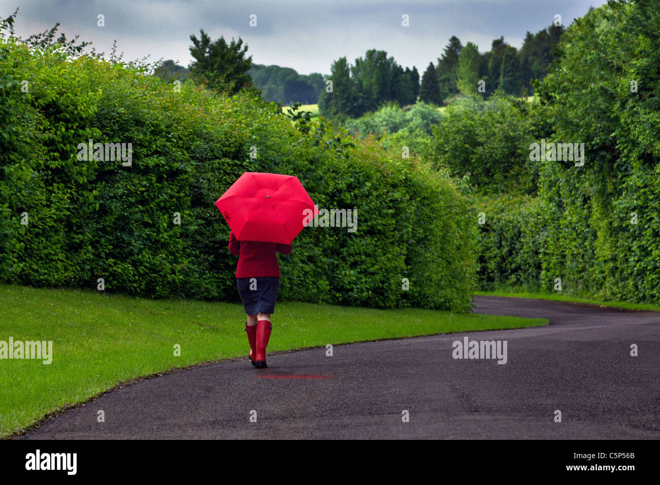 Photo of a woman walking down a road holding a red umbrella after a heavy downpour of rain on an overcast day. - Stock Image