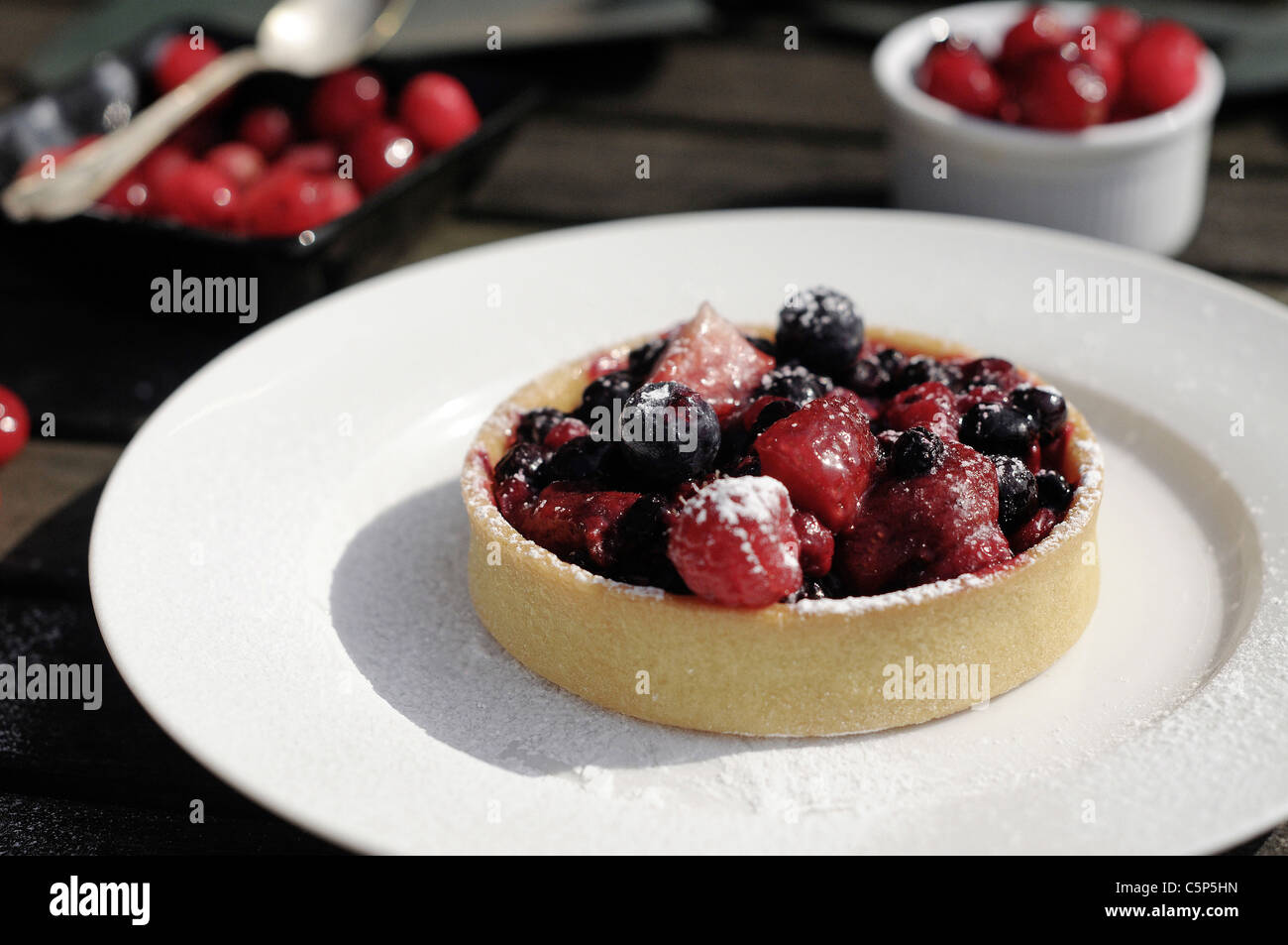Berry tart outside on a white plate - Stock Image
