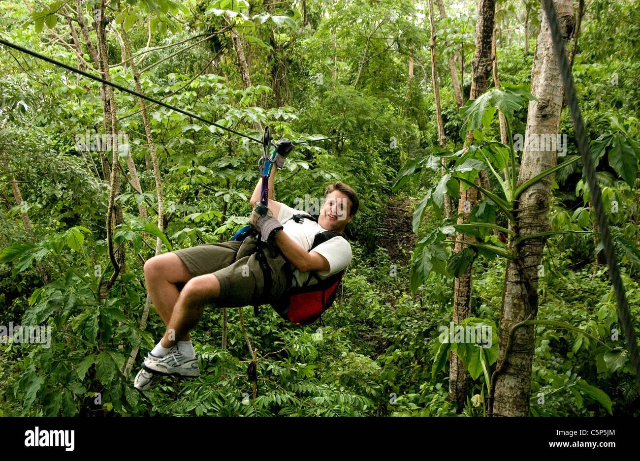 Adventurer on zip line - Stock Image
