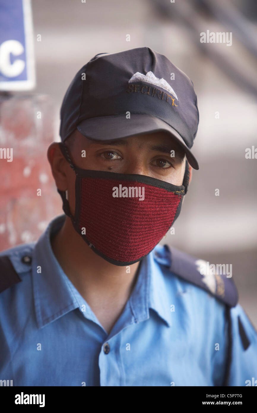 Security guard wearing face mask to avoid pollution, Kathmandu, Nepal, Asia - Stock Image