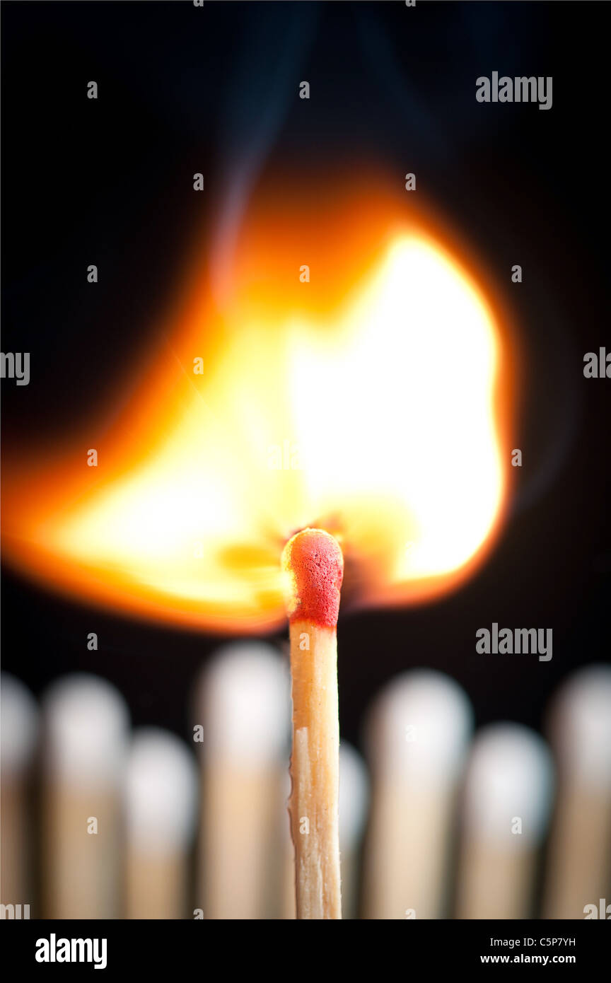 burning match in front of other matches in a row behind it, isolated on black background - Stock Image