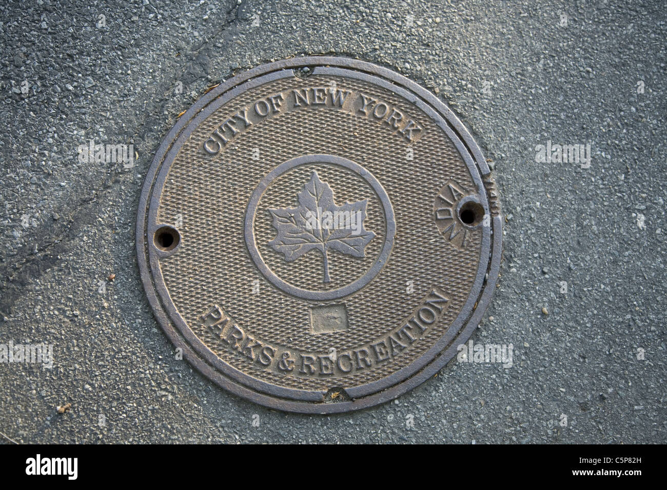 Manhole cover made in India on a road in Prospect Park, Brooklyn, NY. - Stock Image