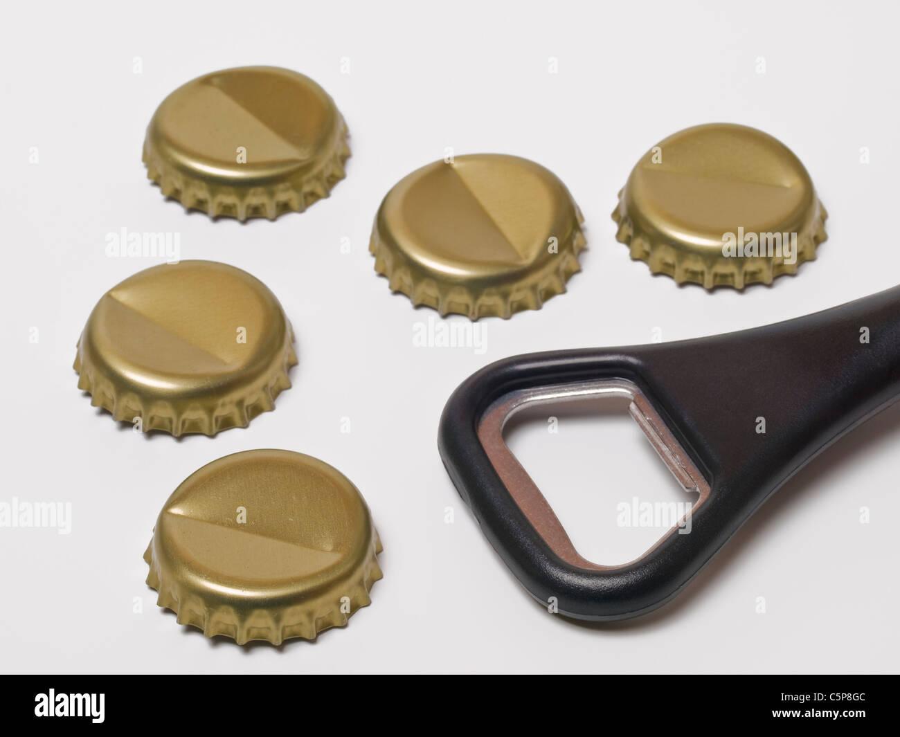 fünf Kronenkorken liegen neben einem Flaschenöffner | five crown corks, beside is a bottle opener - Stock Image