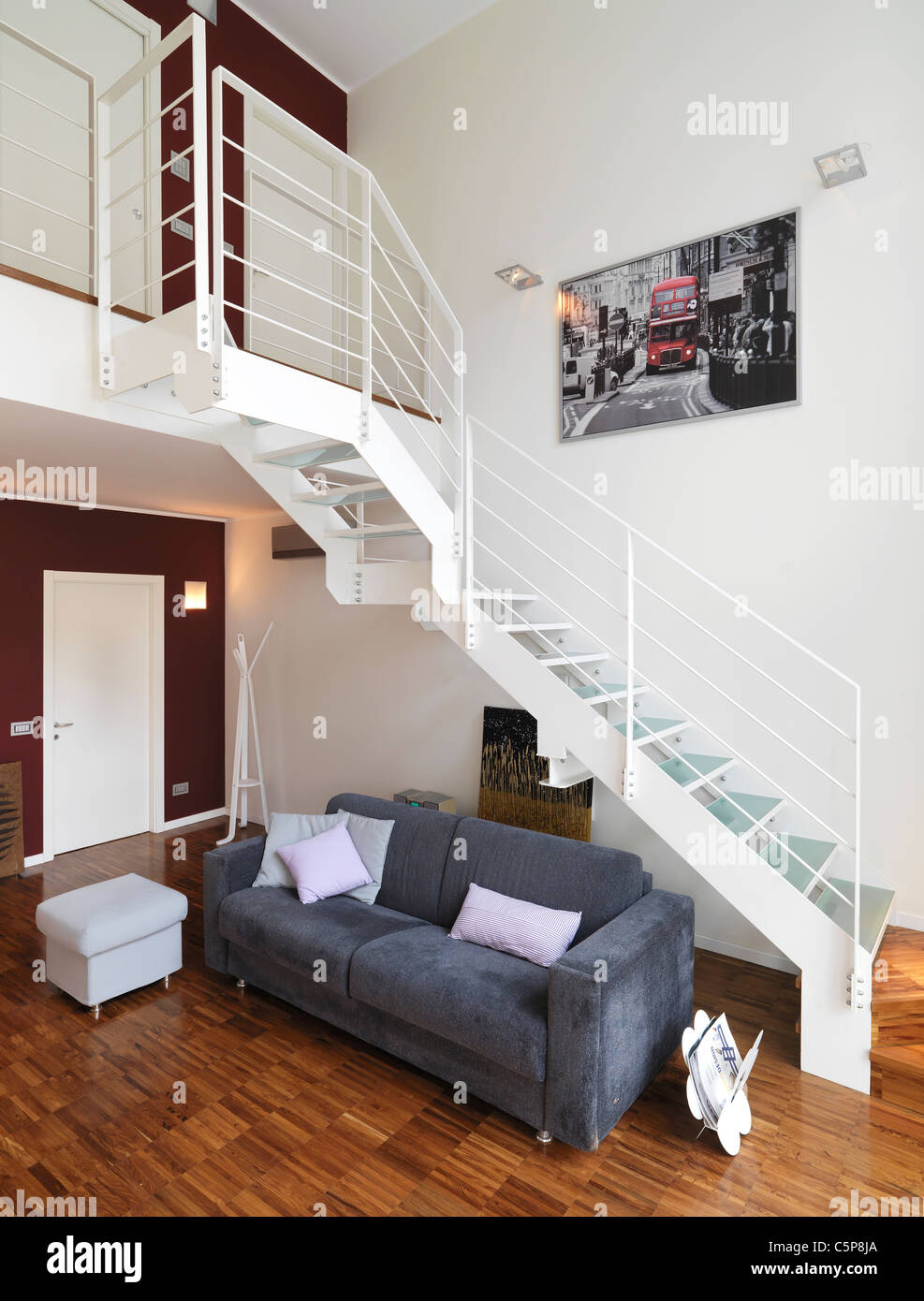 Modern living room with gray sofa under a metal staircase for Divano incassato