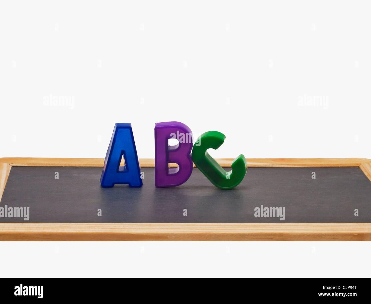 Auf einer Schiefertafel stehen die Buchstaben A, B, C | on a slate are A, B, C upright - Stock Image
