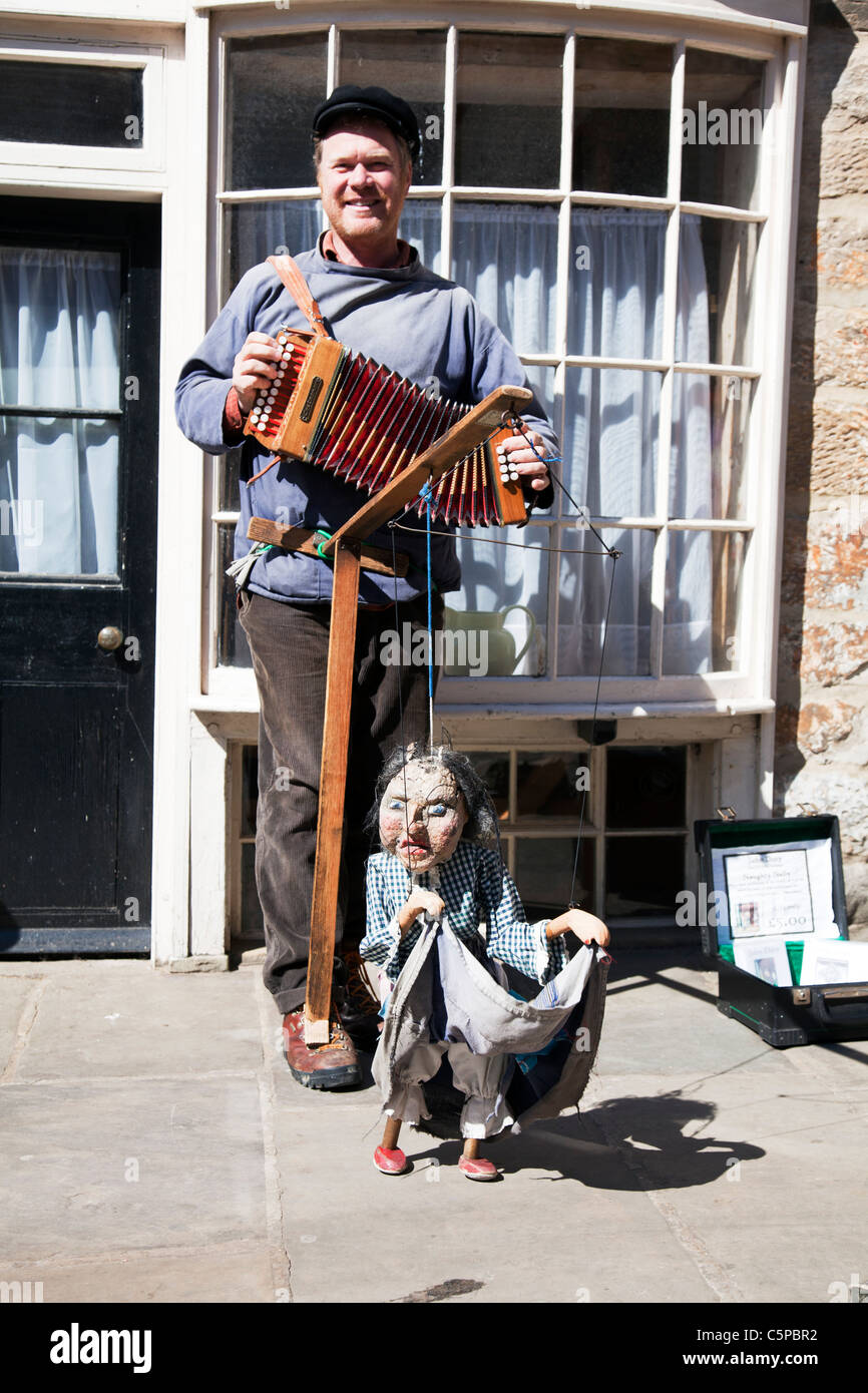 Whitby, Yorkshire, England, street performer with accordion and scary puppet fisher woman on srings - Stock Image