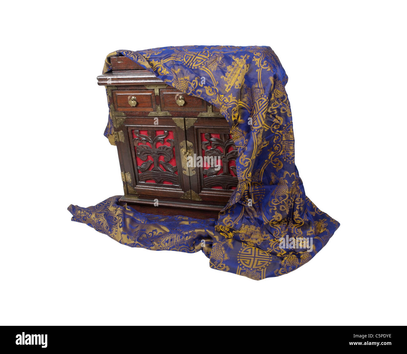 An old chest with small drawers for storing various ingredients covered by a silk scarf - path included - Stock Image