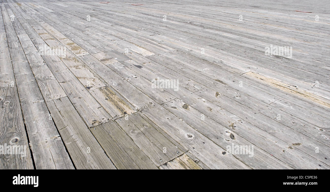 Wooden worn board that make up the pier stretching out the the horizon - Stock Image