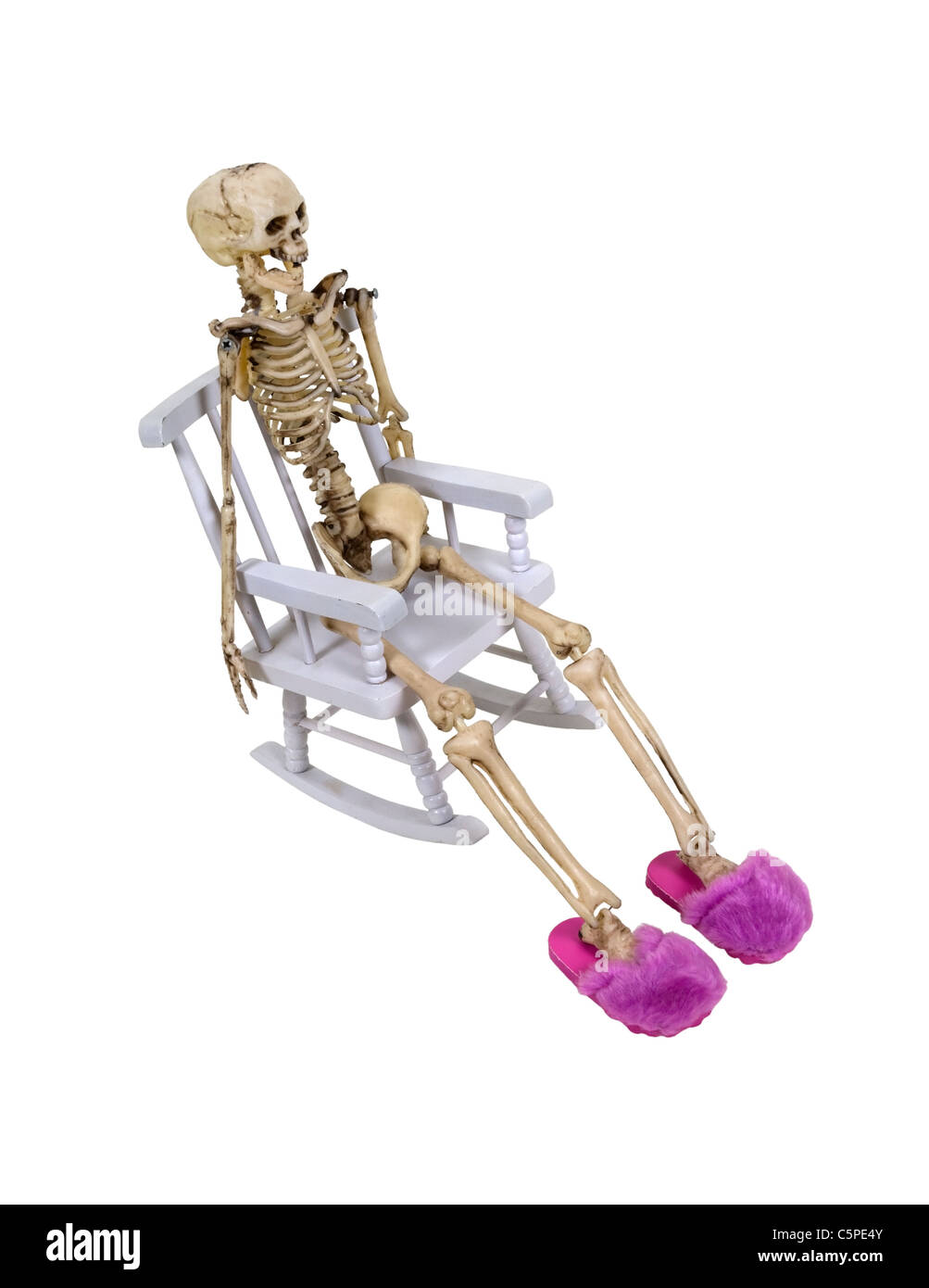A skeleton stretched out in a rocking chair wearing pink fuzzy slippers - path included - Stock Image