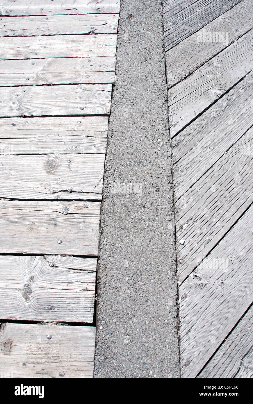 Weatherbeaten wooden walkway laid out in an interesting pattern divided by a cement barrier - Stock Image