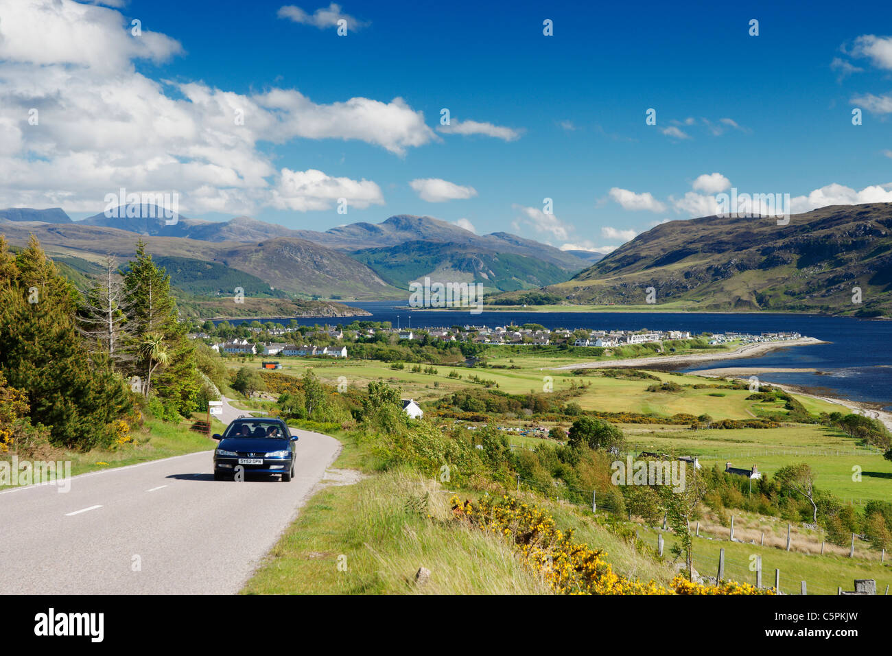 Car on the the A835 main road with view over Ullapool and Loch Broom, Ross and Cromarty, Highland, Scotland, UK - Stock Image