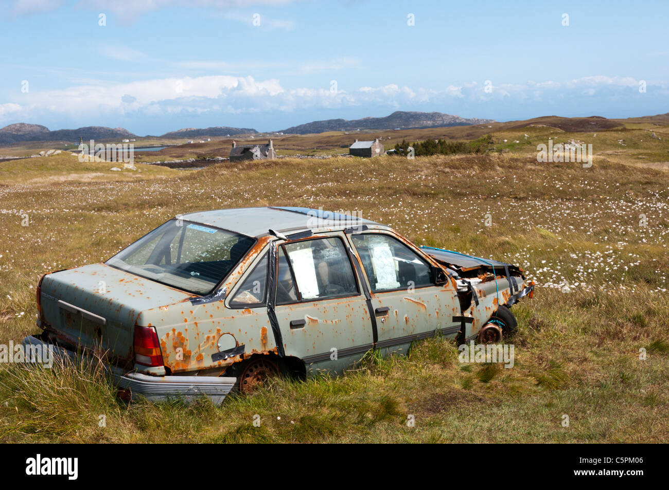 An abandoned car on the island of Flodaigh in the Outer Hebrides. - Stock Image