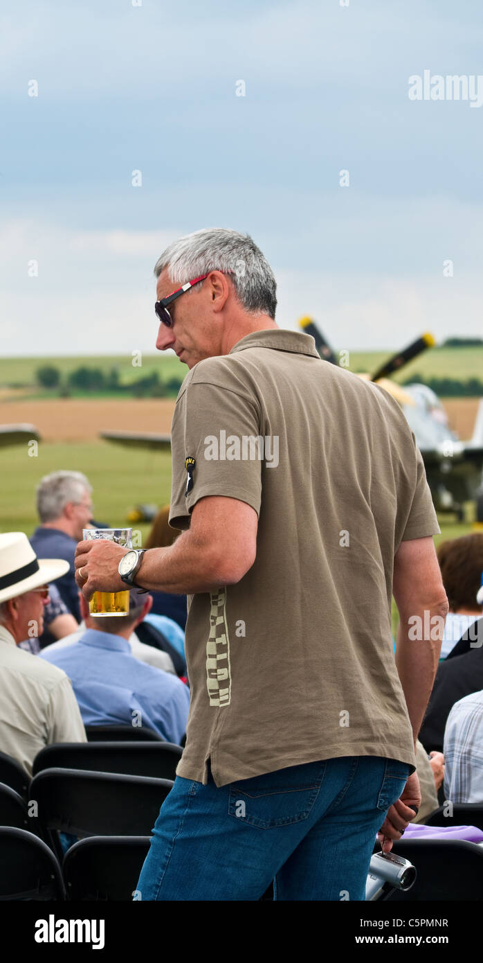 Man at an outside event, talking / listening with a pint of larger - Stock Image