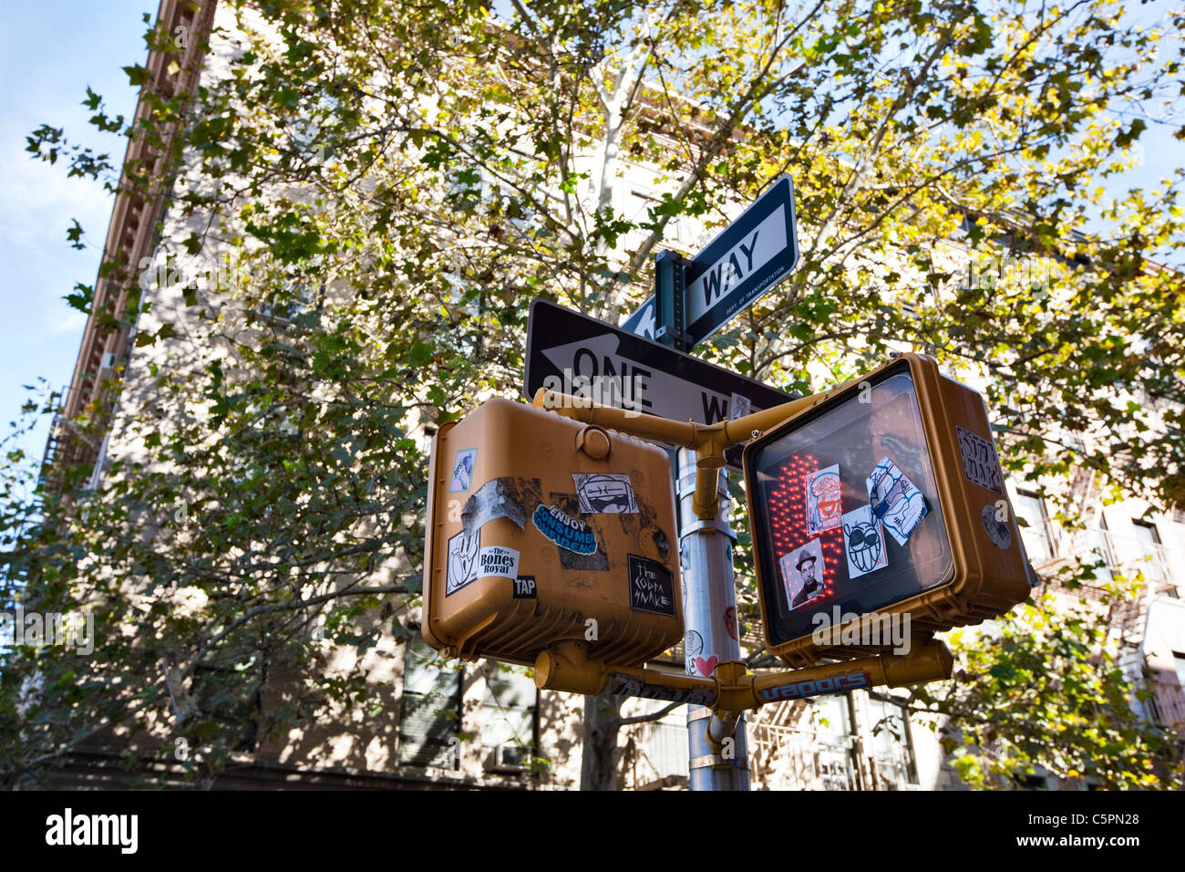 A heavily vandalized crosswalk signal with graffiti and stickers in the SoHo neighborhood of New York city - Stock Image