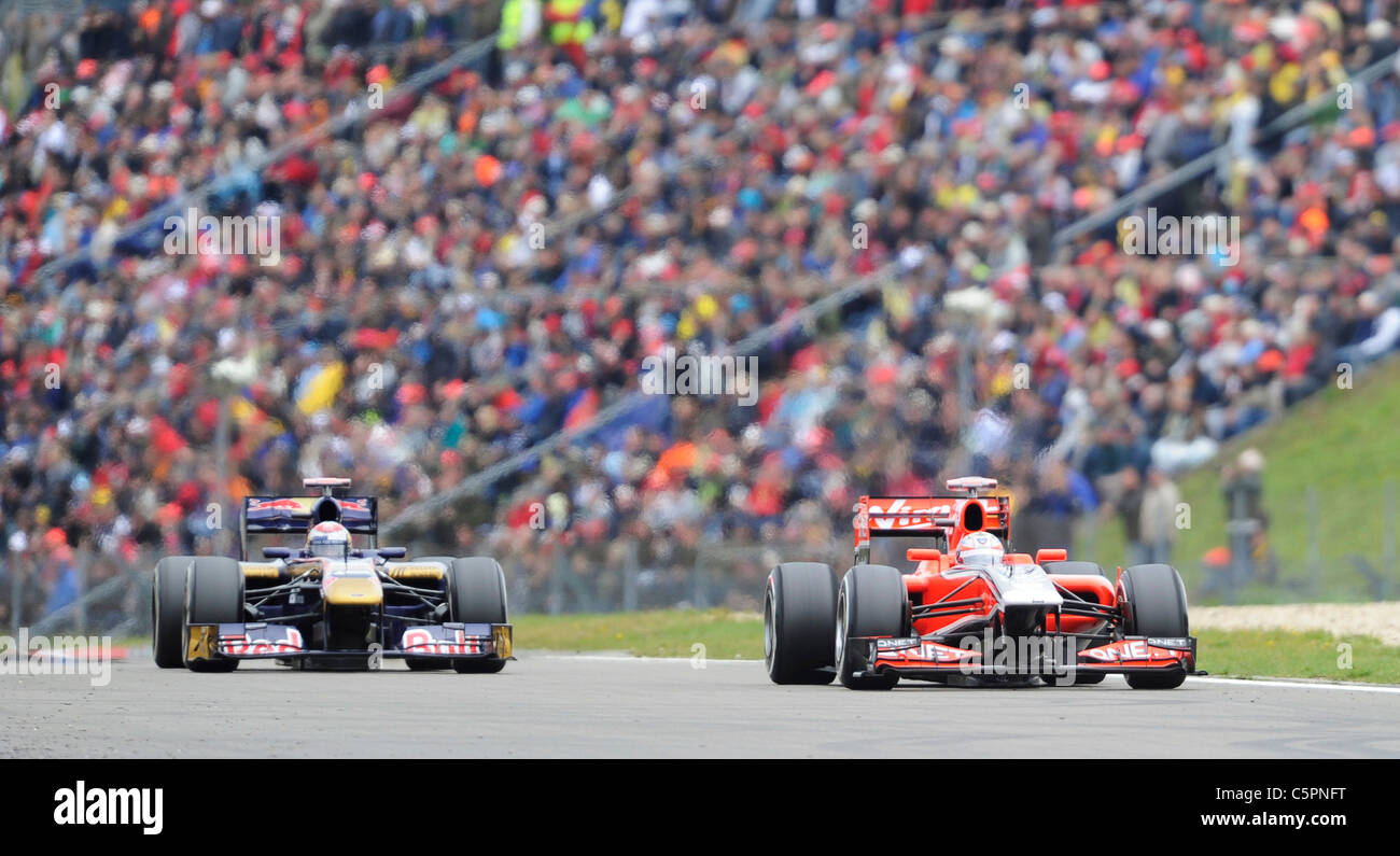 Timo Glock and Sebastien Buemi in front of the crowds at the German Formula One Grand Prix on Nürburgring racetrack - Stock Image