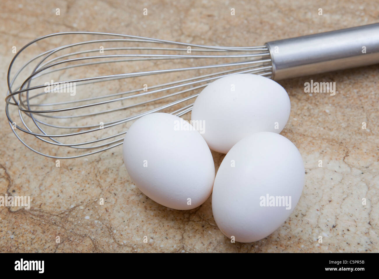 close-up look at whisk and three eggs - Stock Image