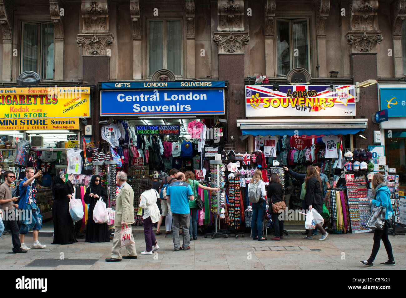 Street Scene of People / Tourists at the Souvenir Shops, Leicester Square, London - Stock Image