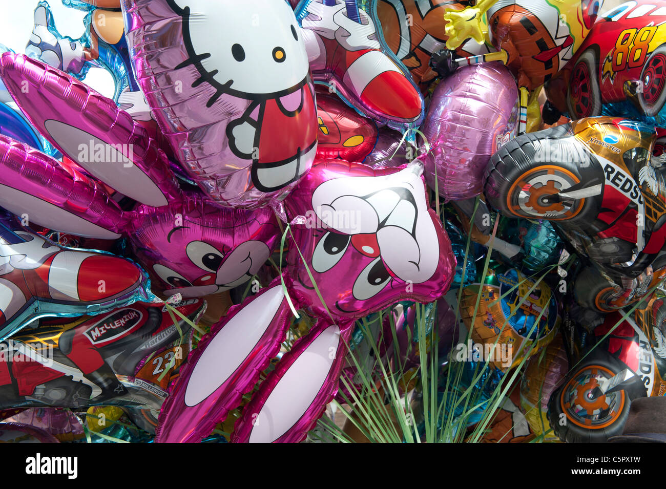 A bunch of inflatable helium balloons featuring children's characters sold on a street in Truro, Conrwall. - Stock Image