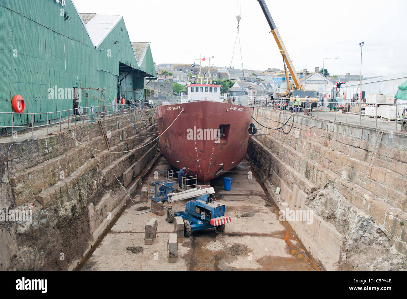 A ship is repaired at a dry dock in Penznace, Cornwall. - Stock Image