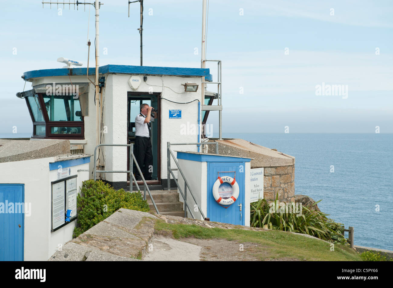 A lifeguard uses binoculars to look out at the sea from a lookout station in St Ives, Cornwall. - Stock Image