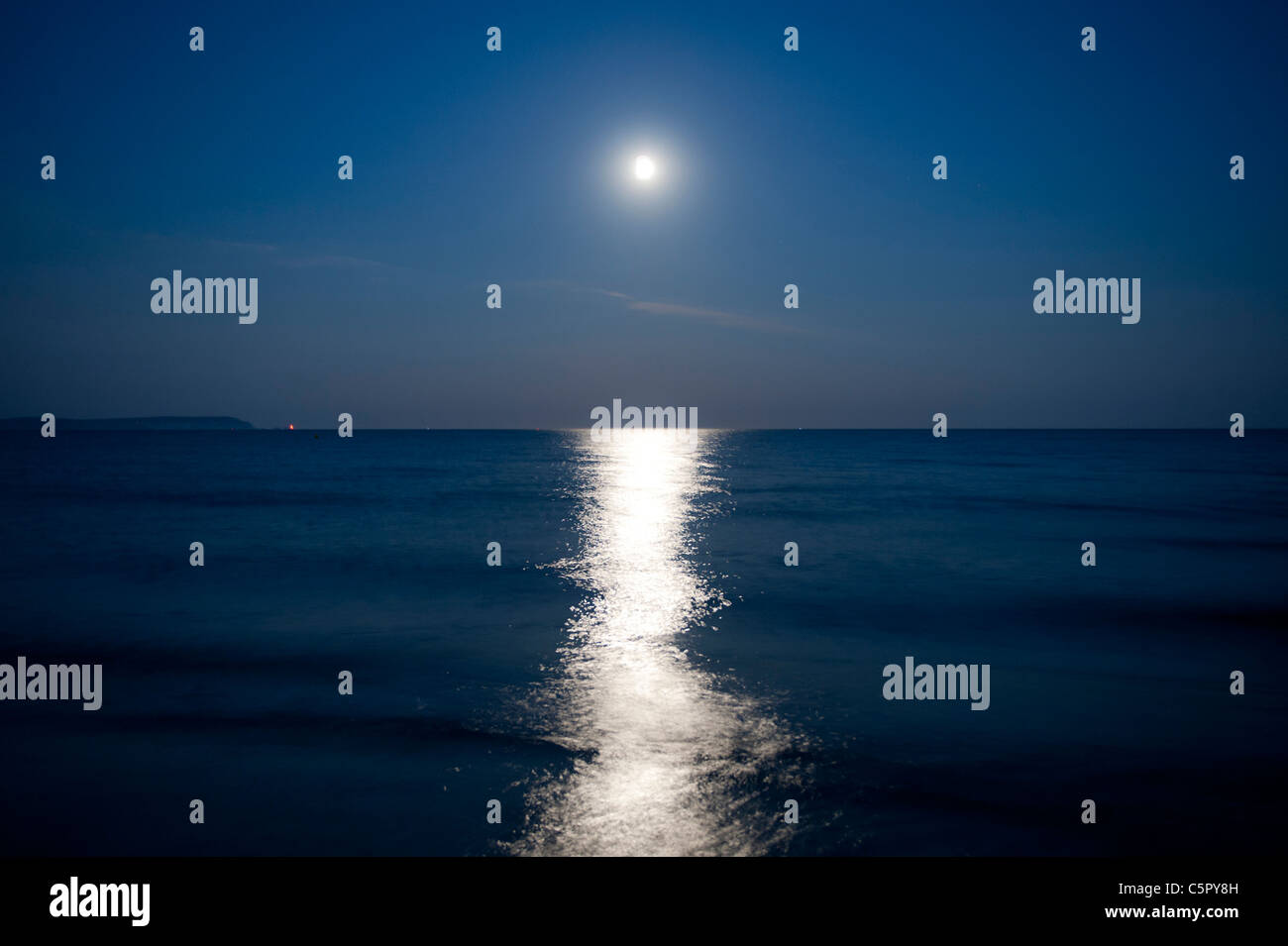 Moonlight sends a reflection over a calm night sea by the coast of Highcliffe, Dorset. - Stock Image