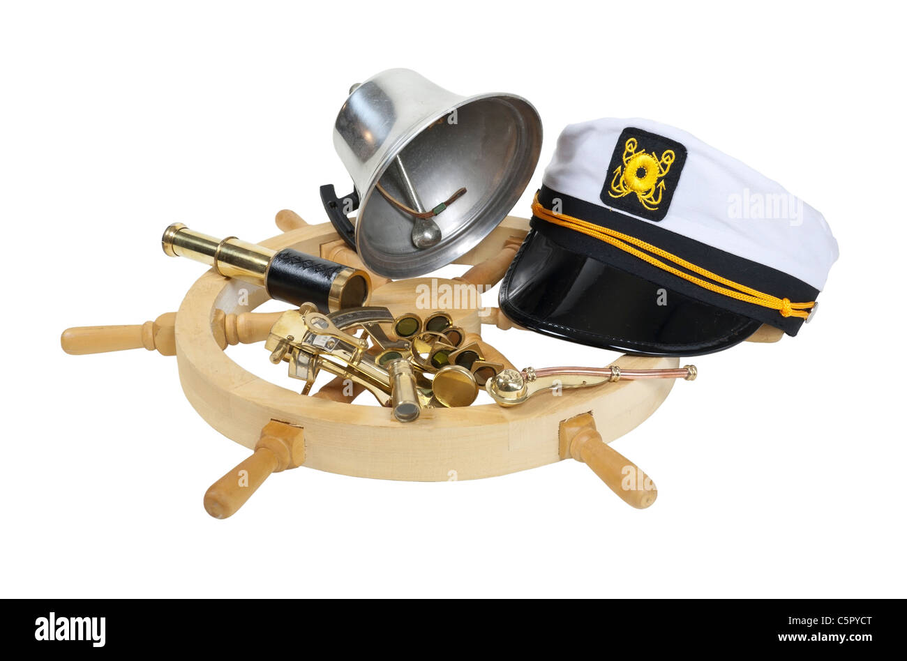 Nautical supplies including ship wheel, captain hat, bell, and an assortment of brass instruments - path included - Stock Image