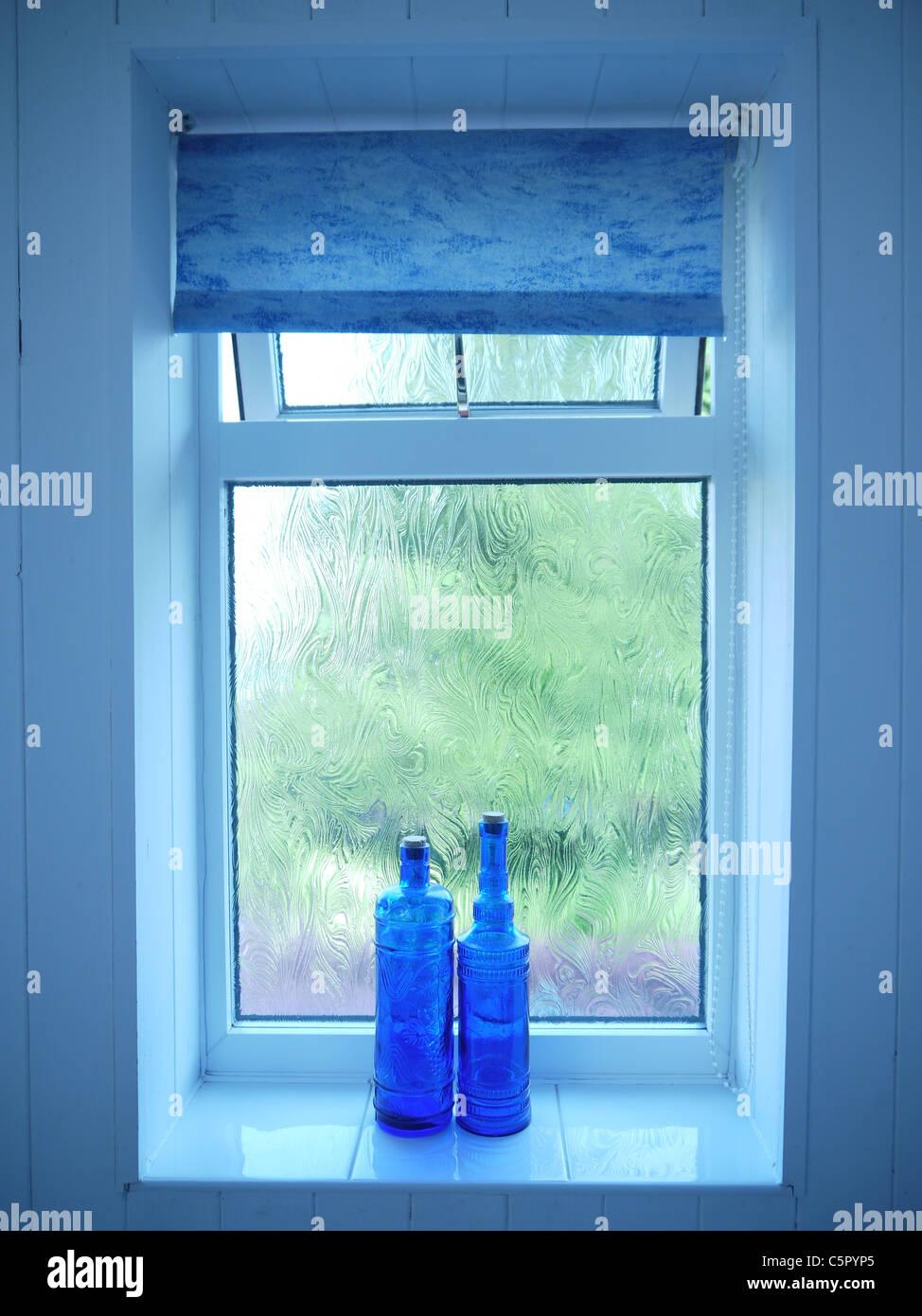 decorative glass bathroom windows two blue decorative bottles sitting on a bathroom window sill  two blue decorative bottles sitting on