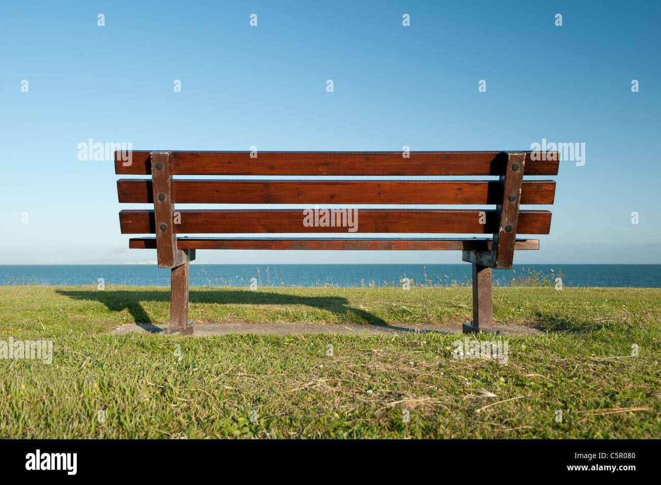 An empty public bench remains unoccupied overlooking a calm and still sea at Mudeford, Dorset. - Stock Image