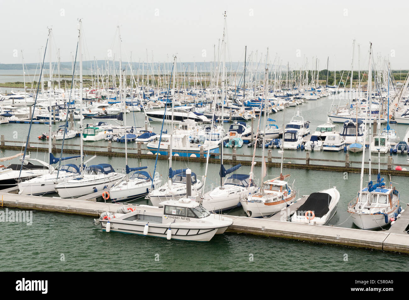 A number of expensive yachts line-up moored in a harbour near to Solent estuary in Lymington, Hampshire. - Stock Image