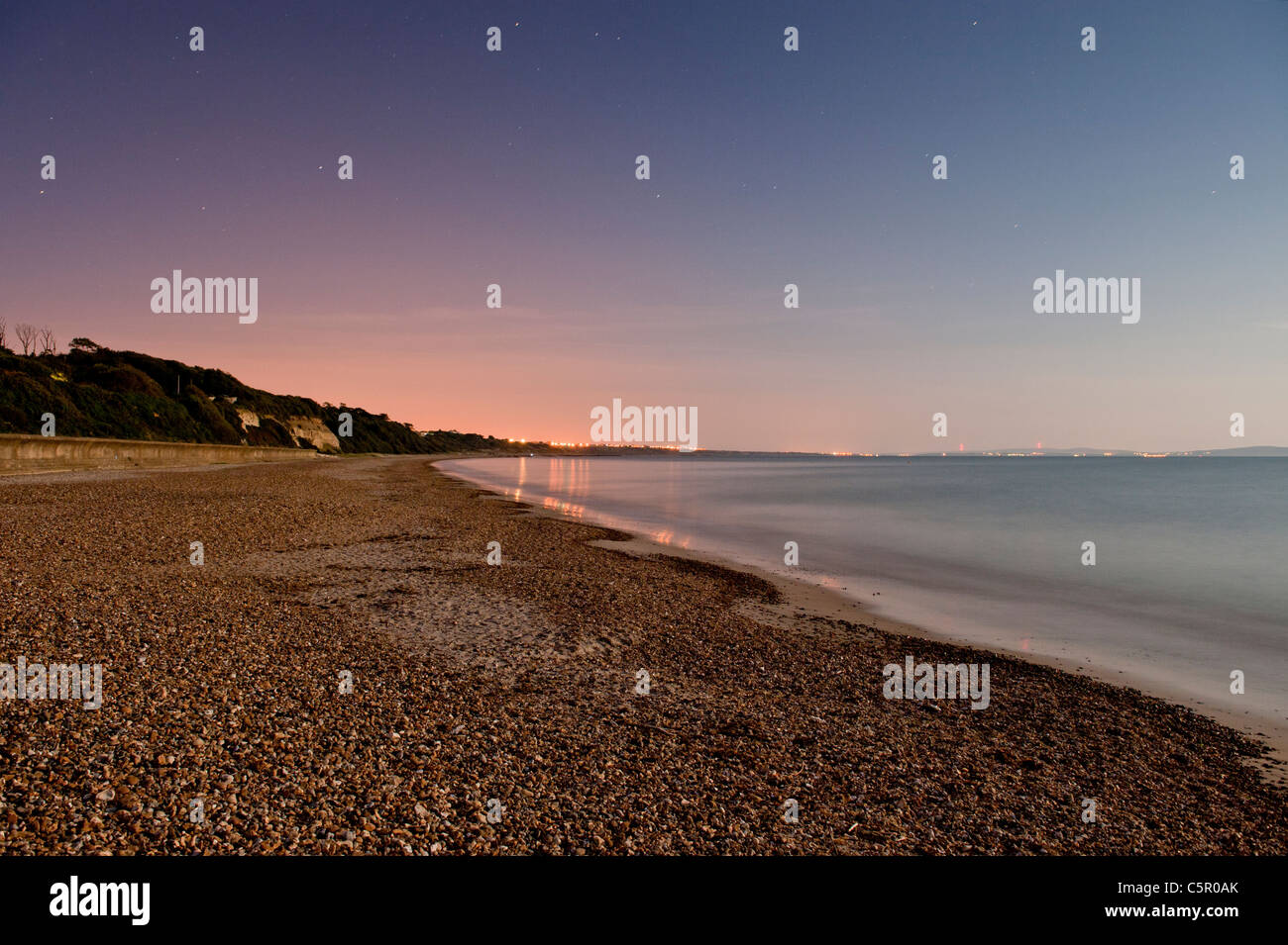 Distant lights reflect off a still night sea by a pebble beach near to Highcliffe, Dorset. - Stock Image