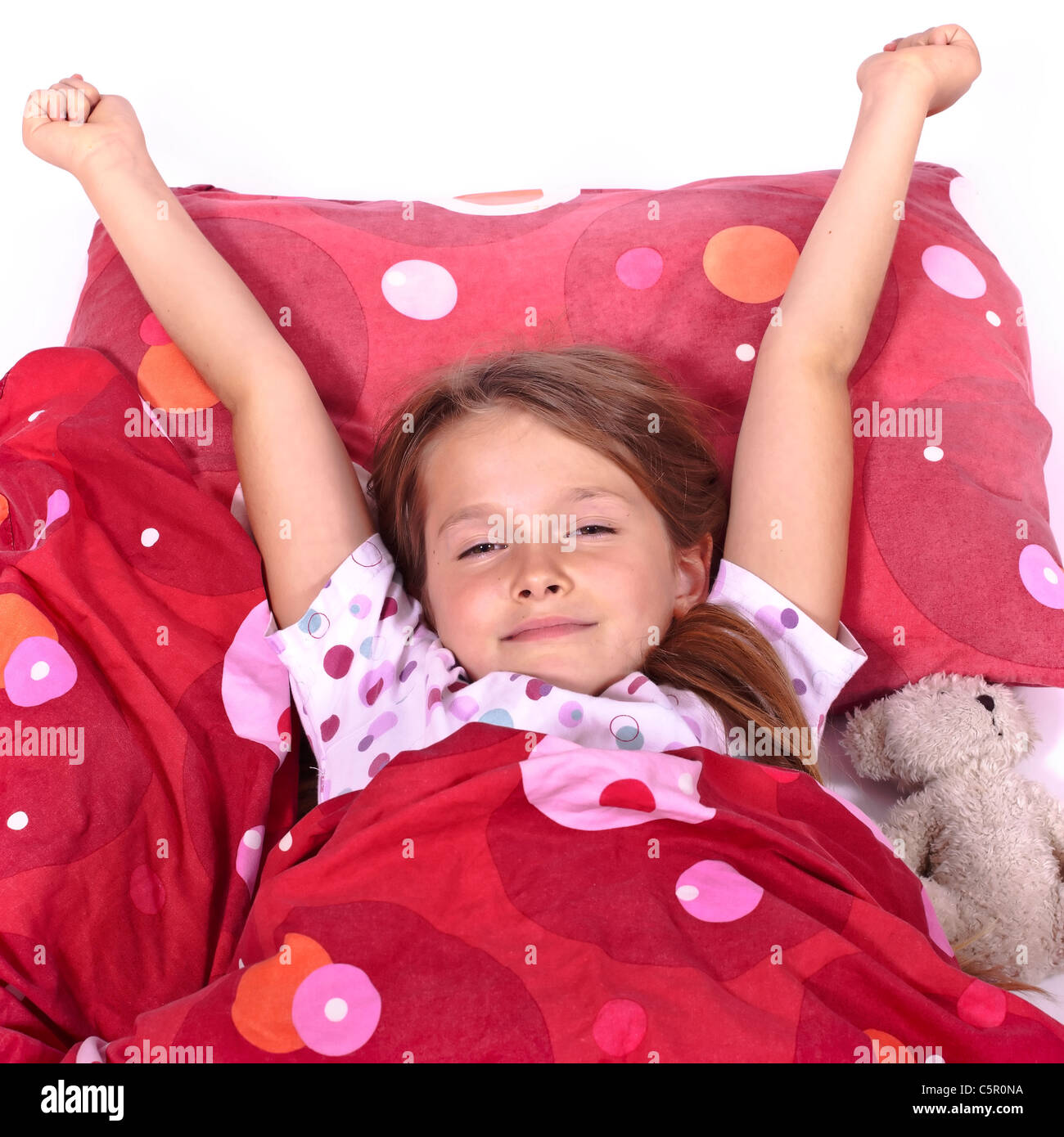 an eight-year-old girl in bed with blanket and pillows and stuffed animals - Stock Image