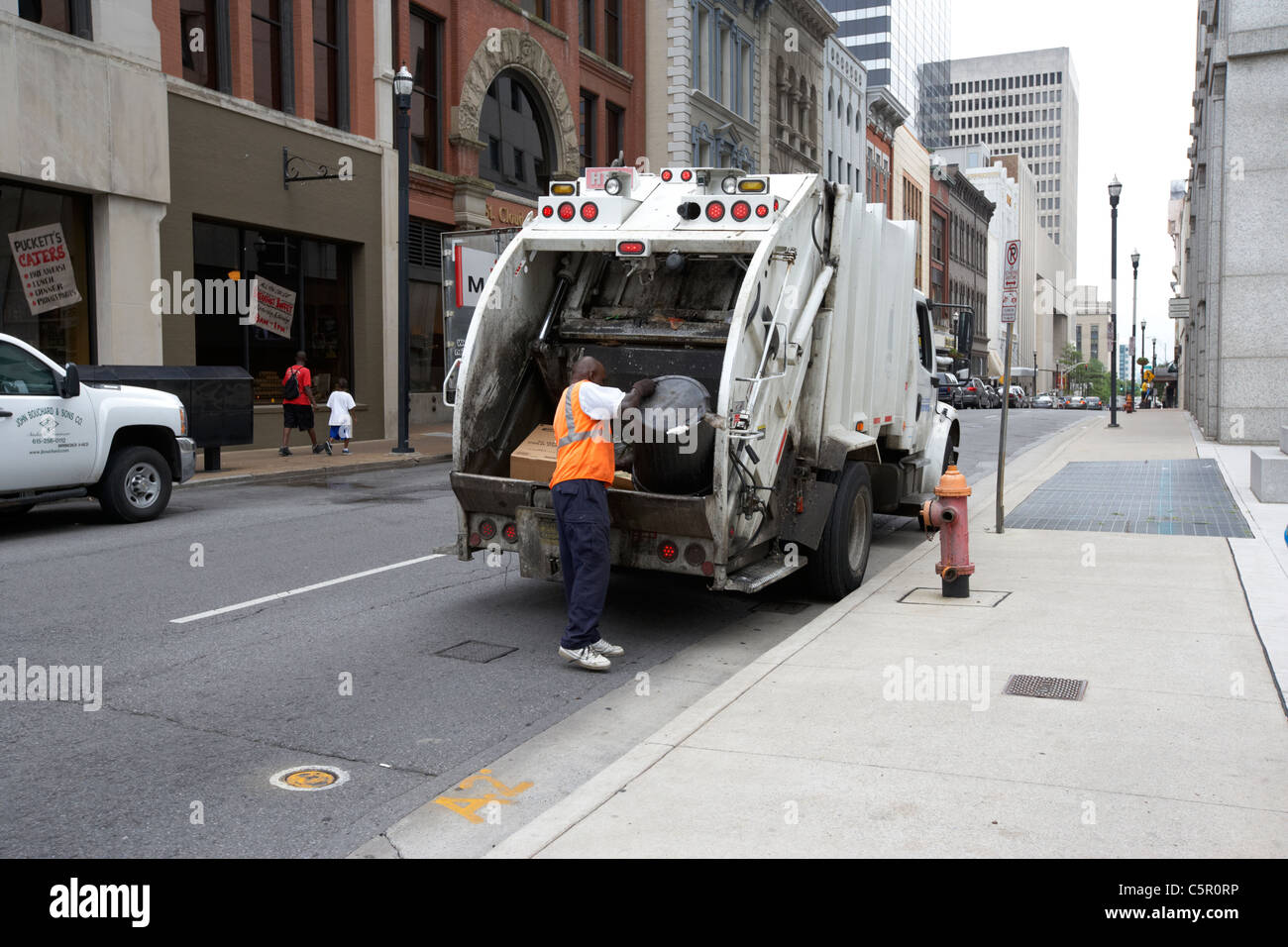 african american city worker emptying garbage can into refuse truck Nashville Tennessee USA - Stock Image